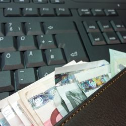 wallet with money in over keyboard